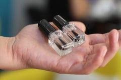 Garrafas transparentes para o verniz para as unhas em uma mão do ` s da mulher Foto de Stock Royalty Free