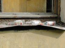 Garrafas vazias da vodca que colocam no peitoril da janela no bairro pobre foto de stock royalty free