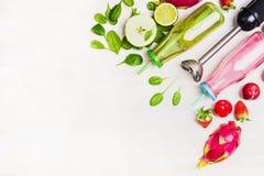 Garrafas verdes e vermelhas do batido com ingredientes frescos e o misturador bonde no fundo de madeira branco, vista superior, b Fotos de Stock Royalty Free