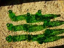 10 garrafas verdes que sentam-se em uma parede Imagens de Stock Royalty Free