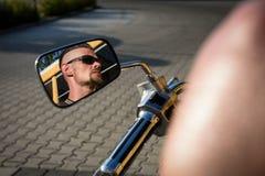 Gars dur avec le dégagement se reflétant dans le miroir de son vélo photo stock