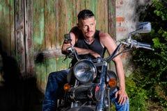 Gars dur avec son vélo devant une porte de grange verte Photos libres de droits