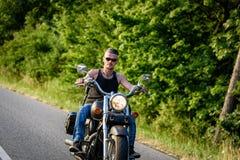 Gars dur sur le vélo de couperet dans le mouvement sur la route Photographie stock libre de droits