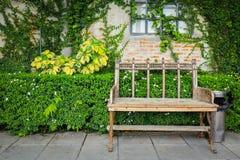 Garten-Bank an blick Wand und am grünen Blatt lizenzfreie stockbilder