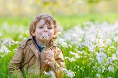 Garten des Kinderjungen im Frühjahr mit blühenden Blumen Stockbilder