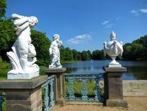 Garten des Schlosses von Charlottenburg in Berlin mit einem See, Bäumen und drei weißen Statuen vor, Deutschland lizenzfreie stockbilder