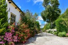 Garten-Eingang mit bunten Blumen und Eisentor Stockfotos