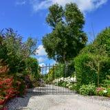 Garten-Eingang mit Vielzahl von blühenden Blumen und von Eisentor Stockbilder
