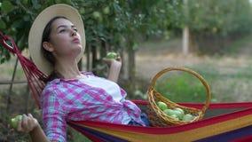 Garten, junge rustikale Frau mit Korb von den Äpfeln, die in der Hängematte stillstehen stock video