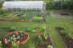 Garten mit Blumenbeeten Rasen und Gewächshaus Stockfotos