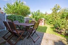 Garten mit dunklen hölzernen Möbeln Lizenzfreies Stockbild