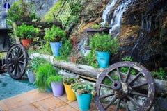 Garten mit kleinem Wasserfall, blühenden Blumen und Wagenrädern stockbild