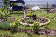 Garten mit Kreisblumenbeet und Rasen Stockbilder