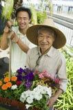 Gartenarbeit des älteren Mannes und des Sohns Stockbild