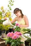 Gartenarbeit - Frau mit Bewässerungsdose und -blumen stockfoto
