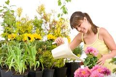 Gartenarbeit - Frau mit strömendem Wasser der Bewässerungsdose Stockbild