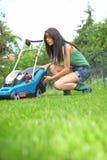 Gartenarbeit, mähendes Gras der Frau mit Rasenmähmaschine lizenzfreie stockbilder