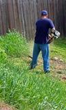 Gartenarbeit und Unkraut whacking stockfotos