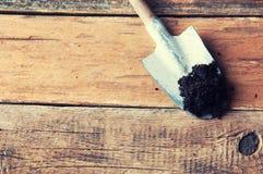 Gartenarbeitspaten auf Holztisch Stockfotos