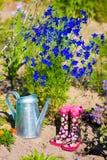 Gartenarbeitstiefel der Gießkanne und der Kinder im Garten Lizenzfreies Stockbild