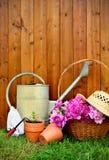 Gartenarbeitwerkzeuge und -gegenstände auf altem hölzernem Hintergrund Stockbilder
