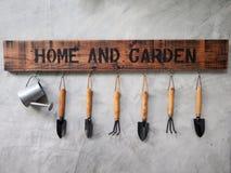 Gartenarbeitwerkzeugfall auf der Betonmauer stockfotos