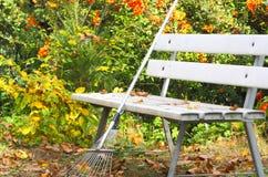 Gartenbank und harken Blätter lizenzfreie stockfotos