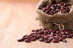 Gartenbohne, rote Bohnen im Sack auf hölzerner Tabelle Lizenzfreies Stockfoto