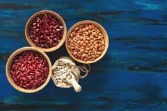 Gartenbohnen in den hölzernen Tellern und weiße Bohnen im Leinenba stockbilder