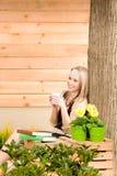Gartenfrauenterrasse genießen Restcupkaffee stockbilder