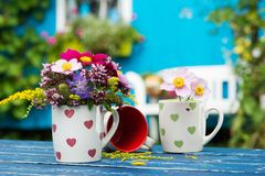 Colorful summer flowers in a coffee cup royalty free stock images