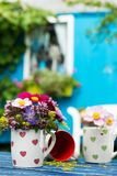 Colorful summer flowers in a coffee cup stock images