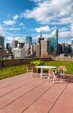 Gartenmöbel auf einem sonnigen Dachspitzenpatio Stockfotografie