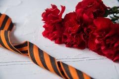 Gartennelken-Blumen und George Ribbon auf abstraktem hellem Hintergrund Siegtag - 9 Jubiläum 70 Jahre Lizenzfreie Stockfotografie