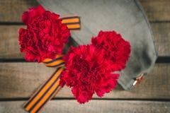 Gartennelkenblumen, George Ribbon und Militärgarnisonkappe mit einem roten Stern 9. Mai Victory Day Stockfotografie