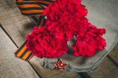 Gartennelkenblumen, George Ribbon und Militärgarnisonkappe mit einem roten Stern 9. Mai Victory Day Lizenzfreies Stockbild