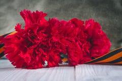 Gartennelkenblumen, George Ribbon und Militärgarnisonkappe mit einem roten Stern 9. Mai Victory Day Lizenzfreie Stockfotografie