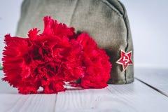 Gartennelkenblumen, George Ribbon und Militärgarnisonkappe mit einem roten Stern 9. Mai Victory Day Stockbild