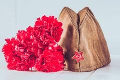 Gartennelkenblumen, George Ribbon und Militärgarnisonkappe mit einem roten Stern 9. Mai Victory Day Lizenzfreie Stockfotos