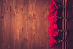 Gartennelkenblumen und George Ribbon-Nahaufnahme auf einem dunklen Hintergrund Siegtag - 9 Jubiläum 70 Jahre Lizenzfreie Stockfotografie