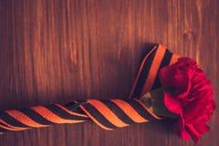 Gartennelkenblumen und George Ribbon-Nahaufnahme auf einem dunklen Hintergrund Siegtag - 9 Jubiläum 70 Jahre Stockfotos