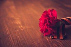 Gartennelkenblumen und George Ribbon-Nahaufnahme auf einem dunklen Hintergrund Siegtag - 9 Jubiläum 70 Jahre Lizenzfreies Stockfoto