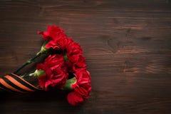 Gartennelkenblumen und George Ribbon-Nahaufnahme auf einem dunklen Hintergrund Siegtag - 9 Jubiläum 70 Jahre Stockbild