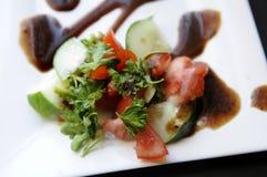 Gartensalat mit rotem vinagraite auf Platte Lizenzfreies Stockbild