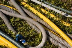 Gartenschläuche wird herauf blaues Band gerollt stockfotos
