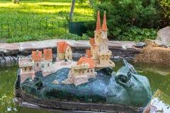 Gartenstatue einer Schnecke mit Schloss auf seiner Rückseite im Teich Lizenzfreies Stockbild