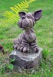 Gartensteinstatue des Hundes auf dem Rasen Lizenzfreie Stockfotos