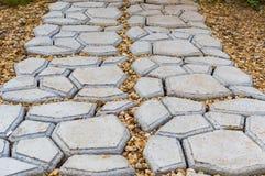 Gartensteinweg mit dem Gras, das zwischen den Steinen heranwächst Stockbild