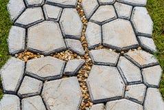 Gartensteinweg mit dem Gras, das zwischen den Steinen heranwächst Stockfotografie