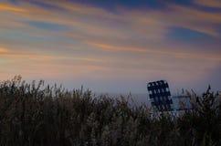 Gartenstuhl auf dem Gebiet bei Sonnenuntergang Stockfoto